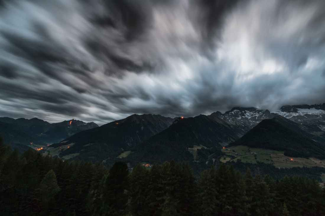 time lapse photography of pine trees near mountains under grey clouds