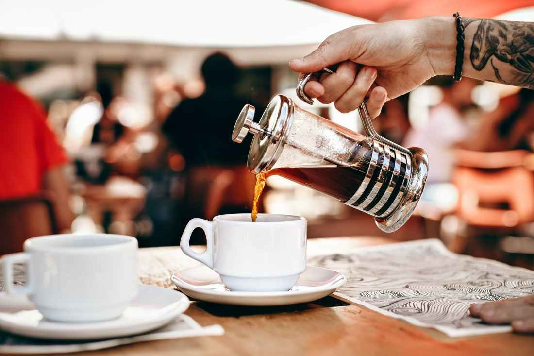 person pouring coffee on white ceramic cup