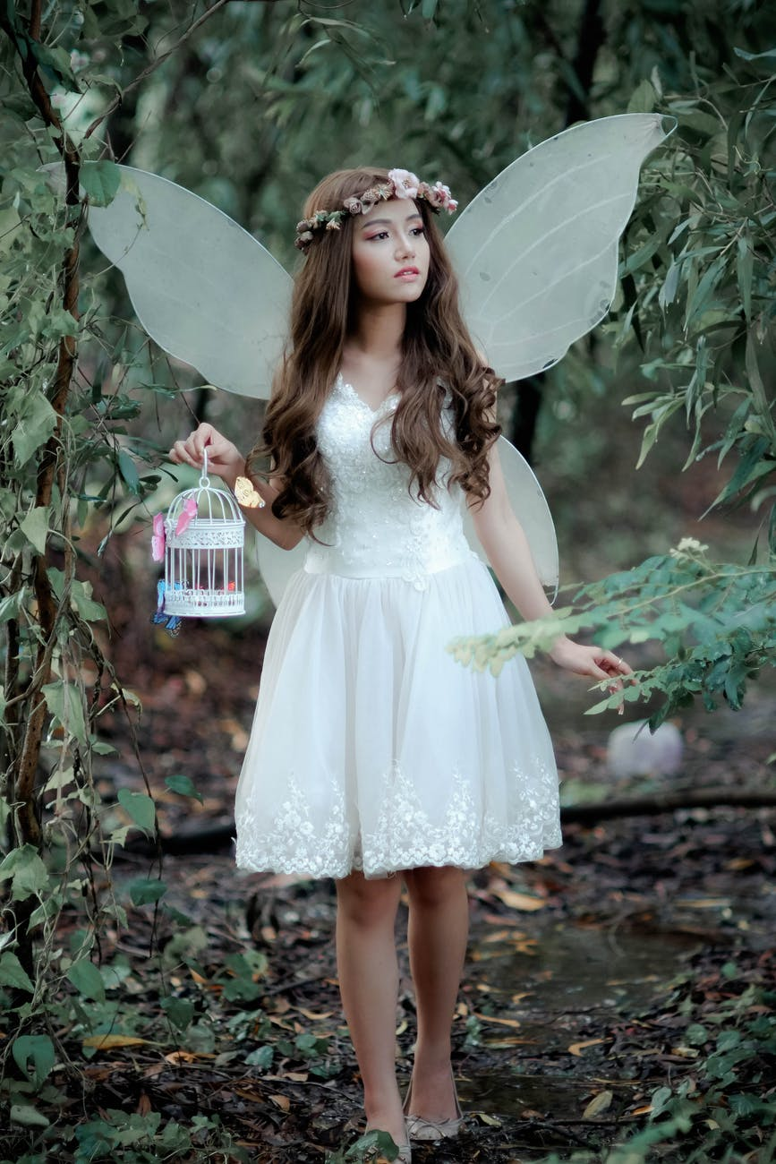 girl holding white birdcage standing behind trees